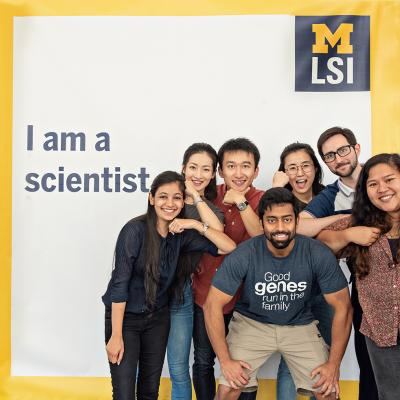 Lab members posing with banner