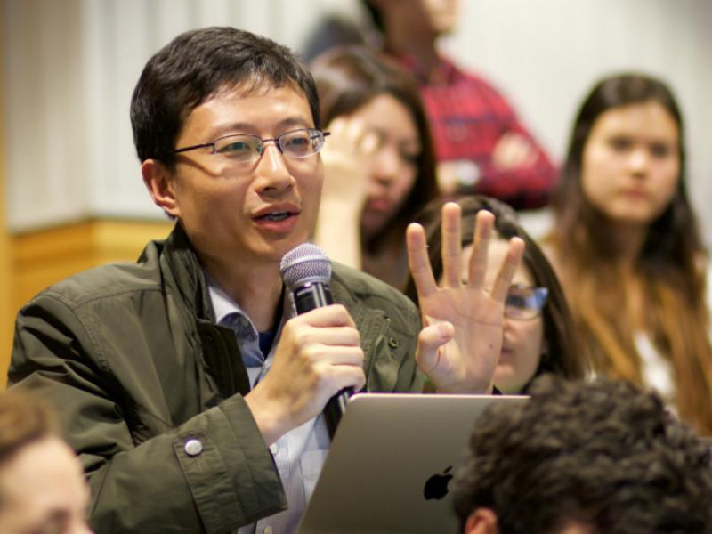 Bin Ye asks a question at a symposium